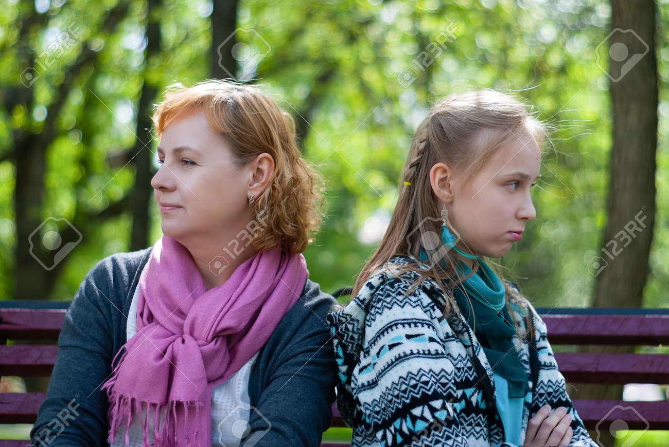 mother and teen daughter are sitting on a park bench in closed poses, turned away from each other, with an angry expression on their faces - 125056339
