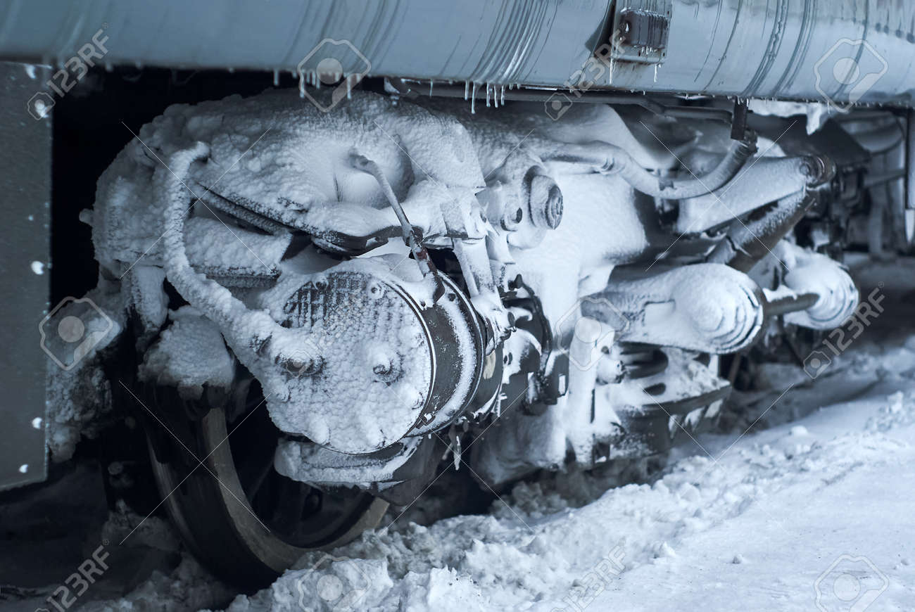 ice and snow covered bogie of a railway passenger carriage on rails during operation in winter - 139508717