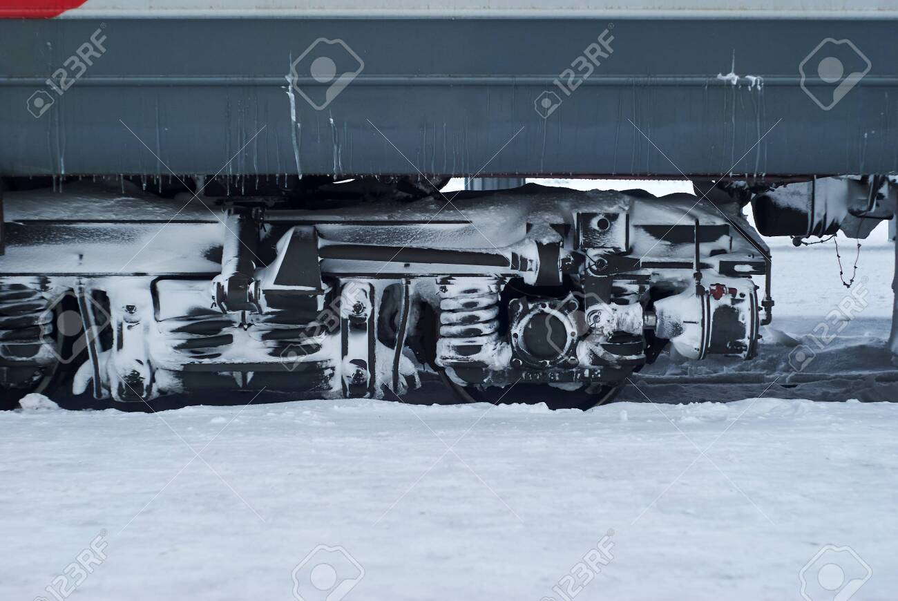 ice and snow covered bogie of a railway passenger carriage on rails during operation in winter - 139508557
