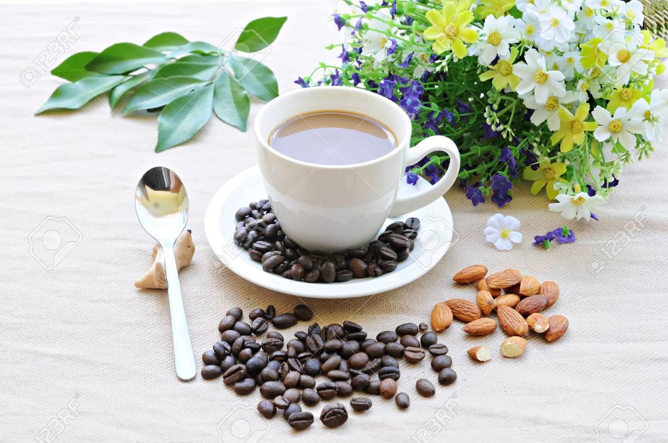 Café para todos...... - Página 2 30809604-taza-caliente-de-caf-almendras-granos-de-caf-con-flores-de-fondo-Foto-de-archivo