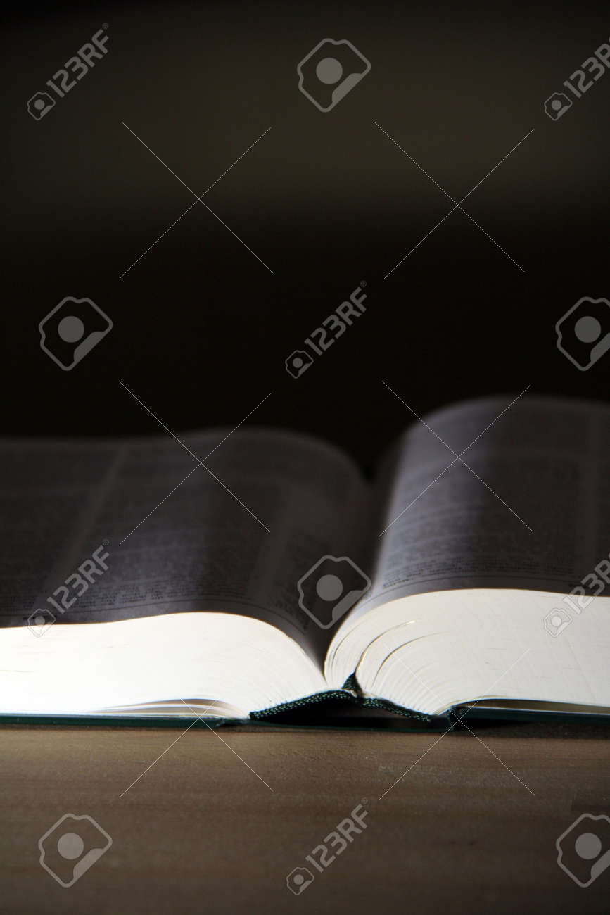 opened pages of a book on wooden table Stock Photo - 6088594