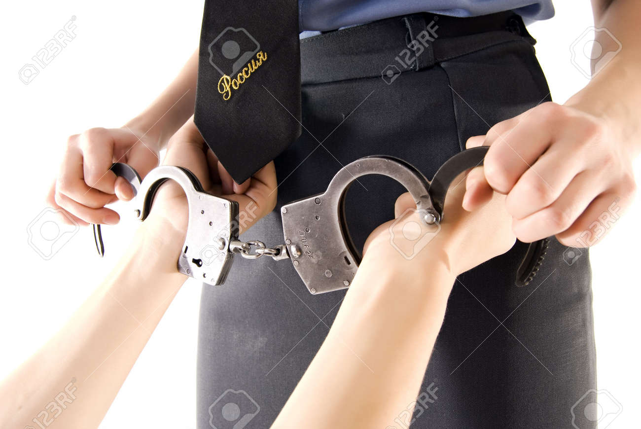 Young woman in police uniform putting handcuffs on someone Stock Photo - 8172617