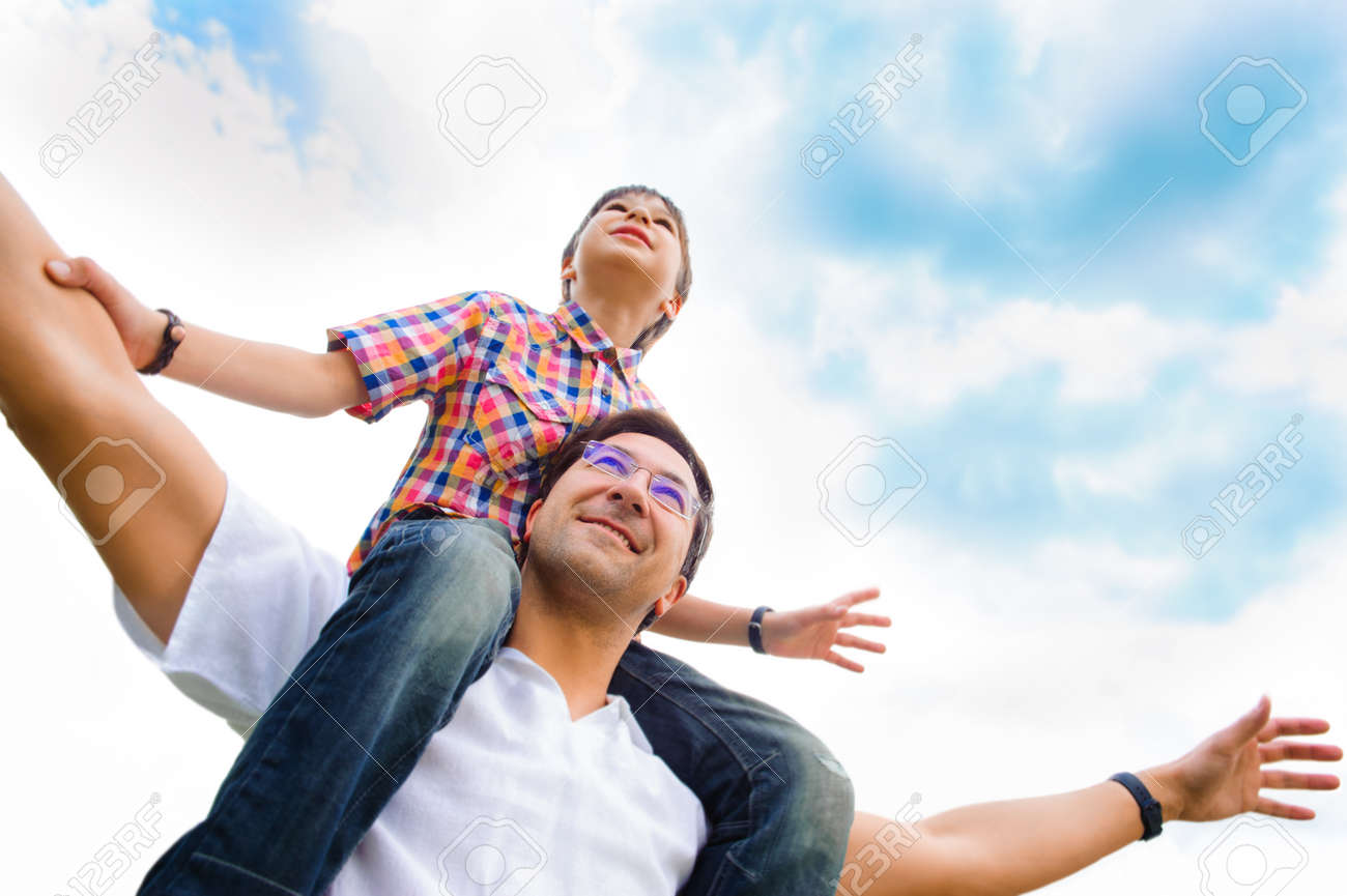 Portrait of smiling father giving his son piggyback ride outdoors against sky Stock Photo - 28173546