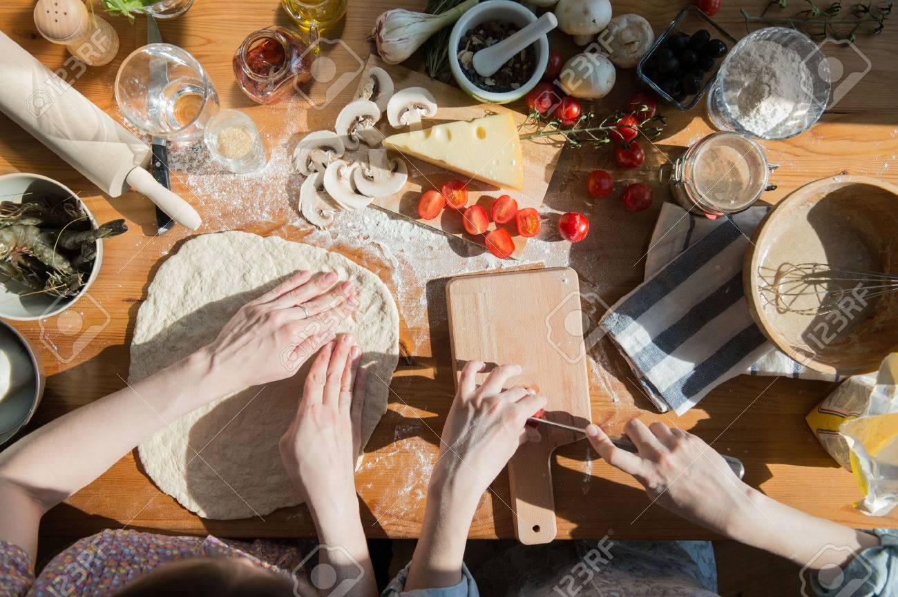 archivio fotografico due donne di pizza cucinare a casa riempimento pizza con gli ingredienti vista dallalto vista ambientale