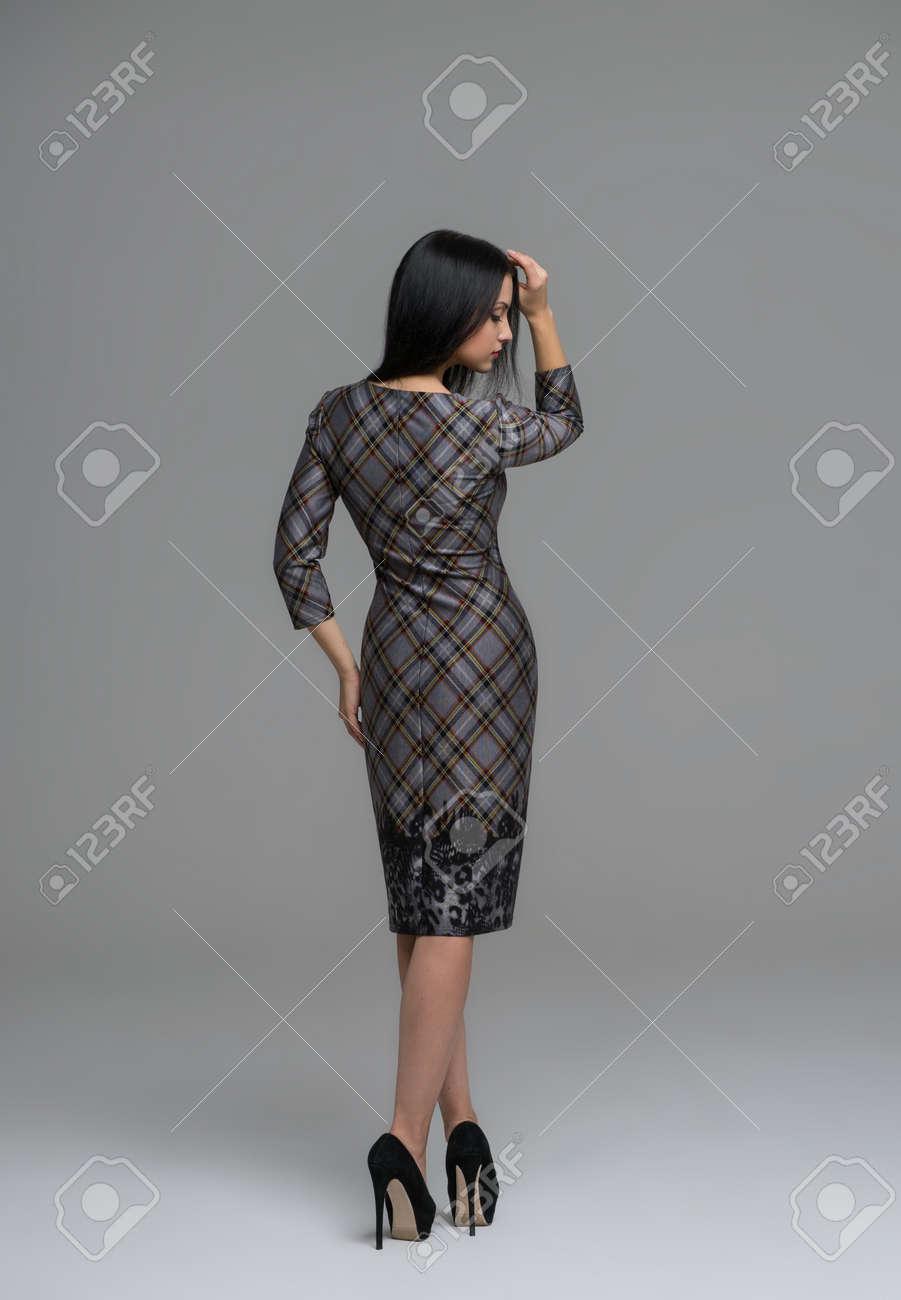 完全な長さのファッションのドレスの後ろ姿のセクシーなブルネット女性の肖像画