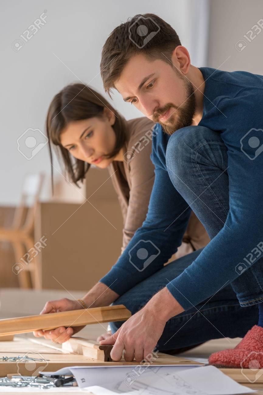 Glückliche Junge Paare, Die Zusammenselbstmontage Möbel, Wie Sie In Ihr Neues  Haus Zu Bewegen