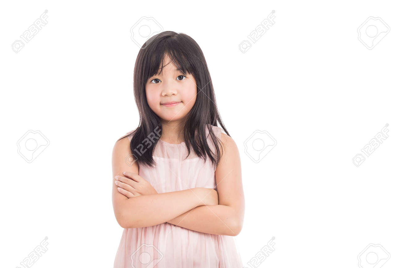 Portrait Of A Little Asian Girl Standing With Folded Hands Over White Background Stock Photo