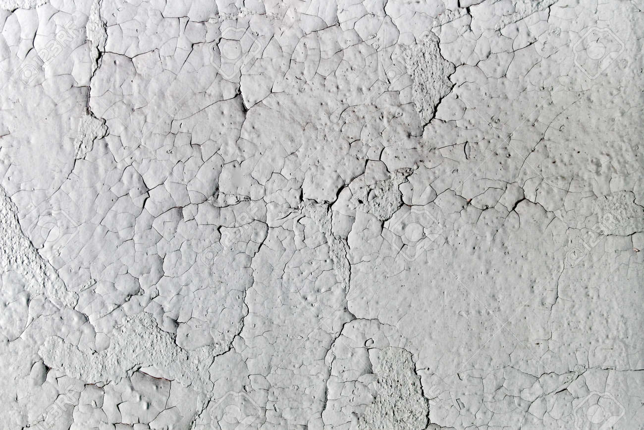 Aged Cracking And Textured White Paint On An Old Wall Stock Photo