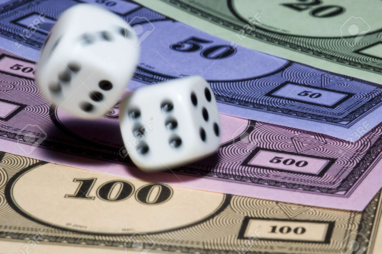 Rolling dice with move effect on monopoly money Stock Photo - 649859
