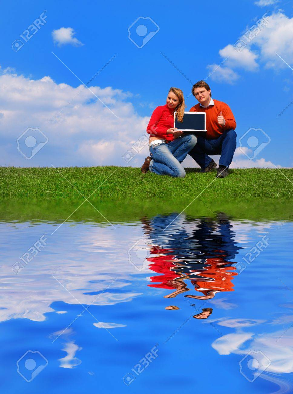 Couple with notebook sitting on grass against sky with reflection on water Stock Photo - 874214
