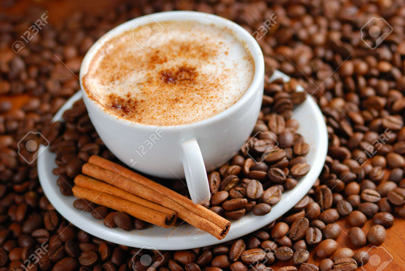 Cup of cappuccino  with cinnamon and spilled out coffee beans. Stock Photo - 1281870