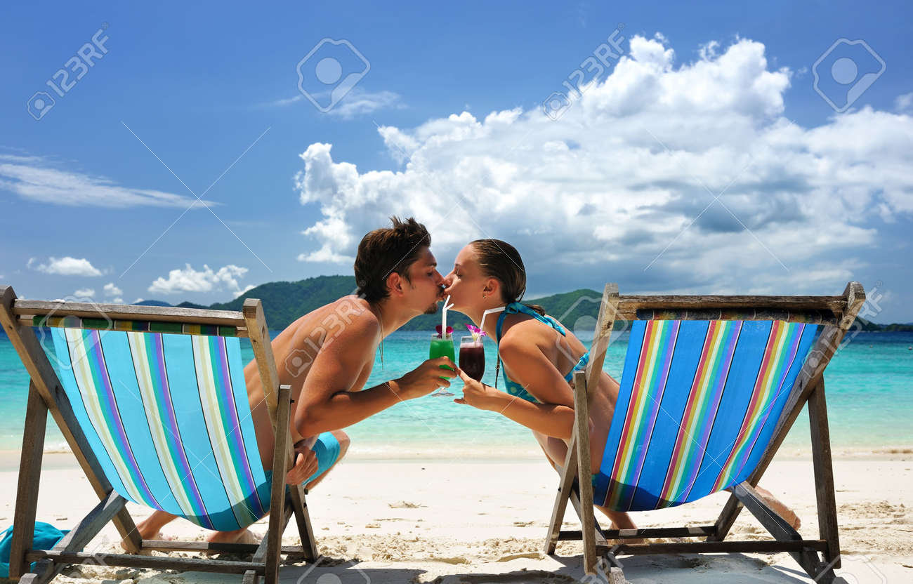 Couple on a tropical beach in chaise lounge Stock Photo - 6557595