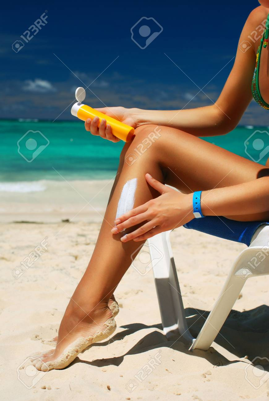 Tan woman applying sun protection lotion Stock Photo - 6632875