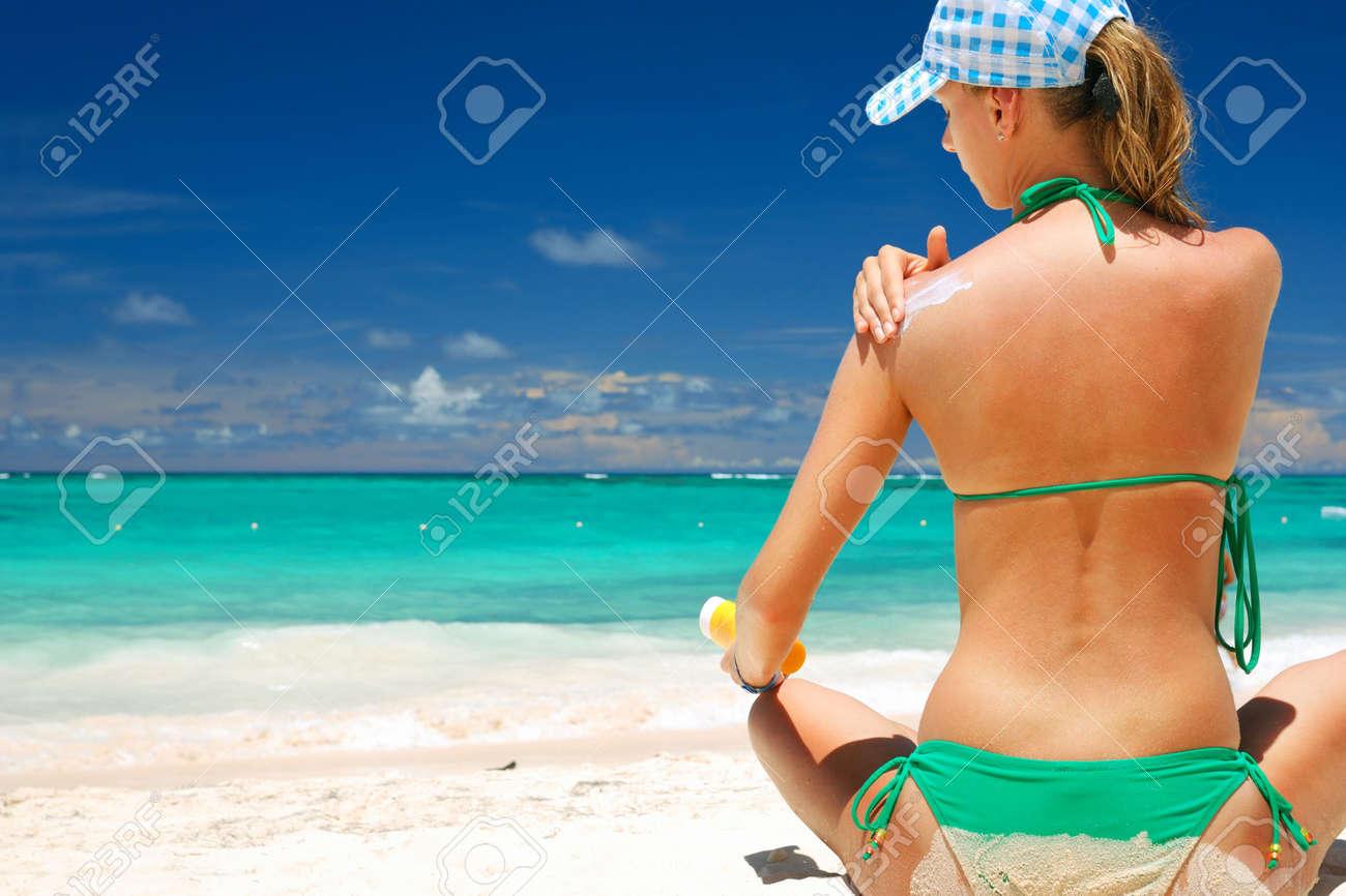 Tan woman applying sun protection lotion Stock Photo - 6681203