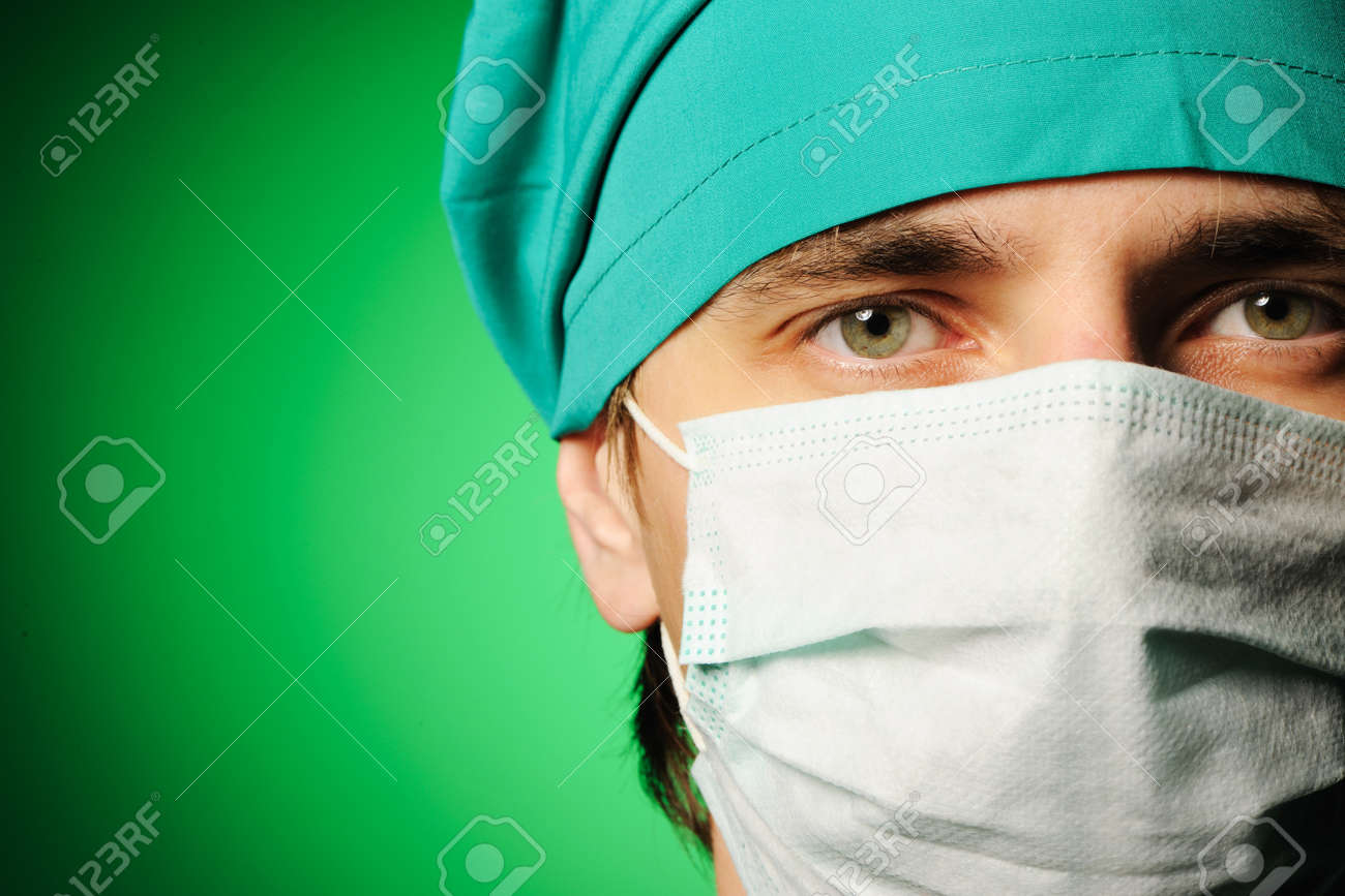 Surgeon in mask over green Stock Photo - 7917352