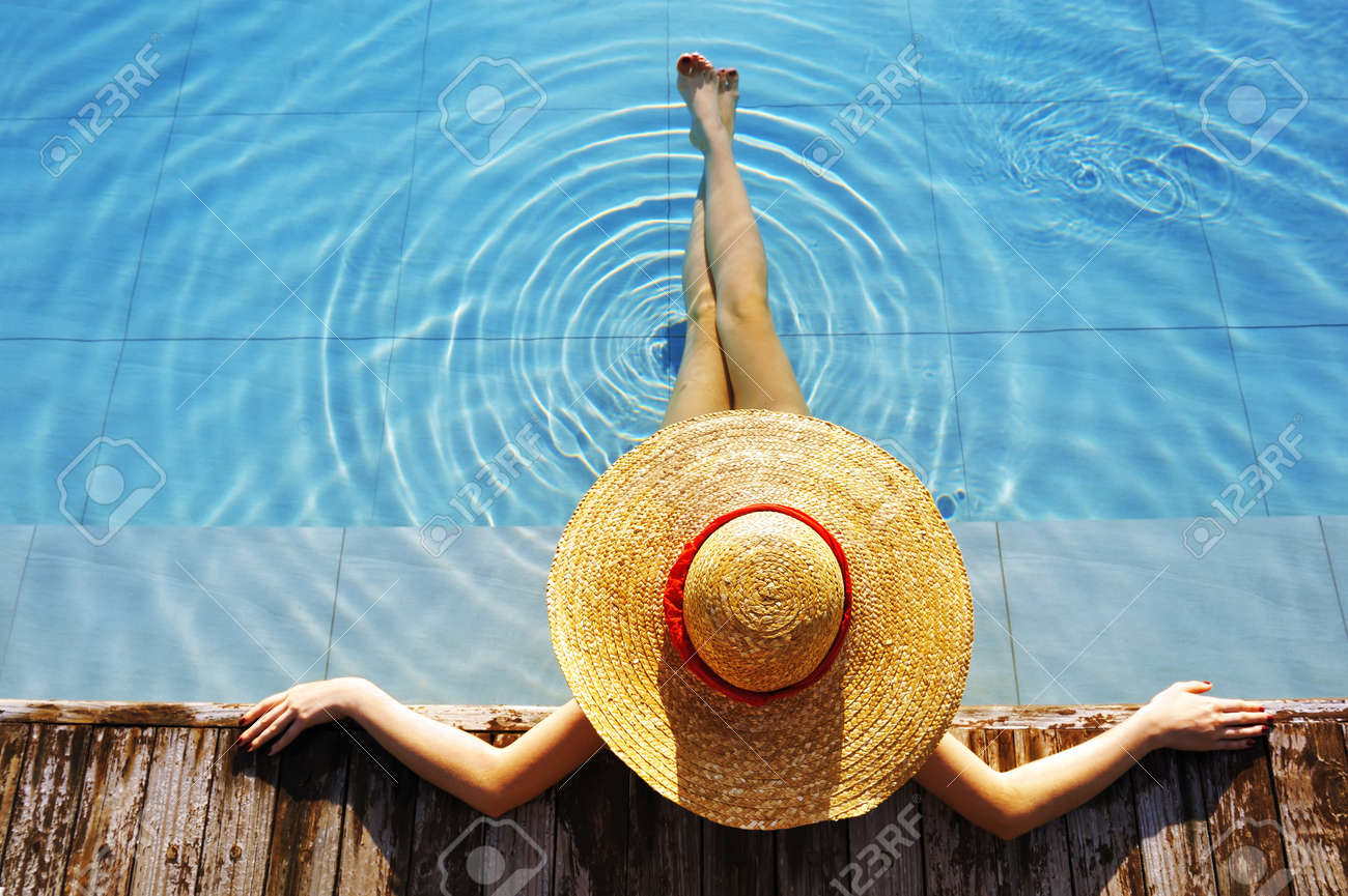 Woman in hat relaxing at the pool Stock Photo - 8548943