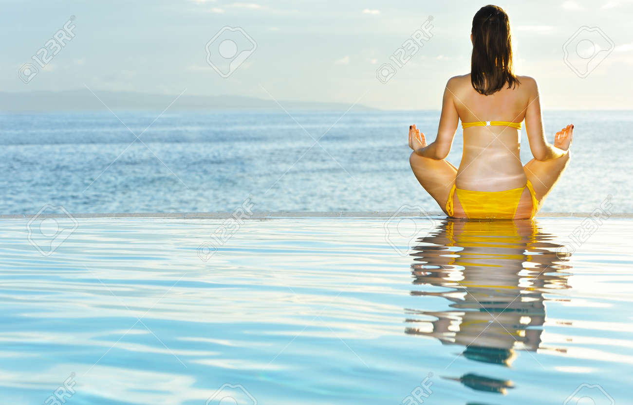 Woman doing yoga exercise at poolside Stock Photo - 8829687