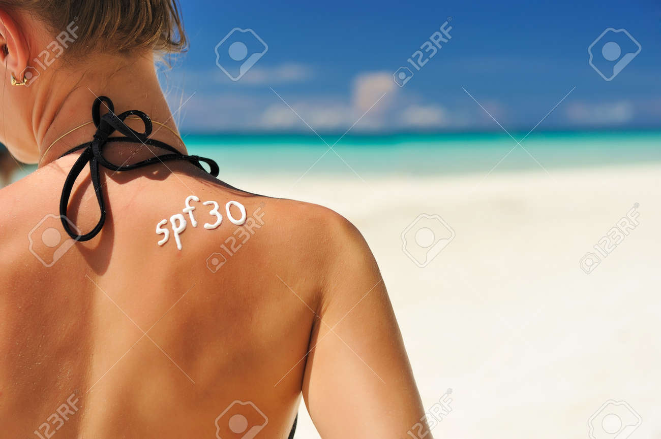 Sunscreen lotion over tan woman skin made as SPF 30 word Stock Photo - 9736601
