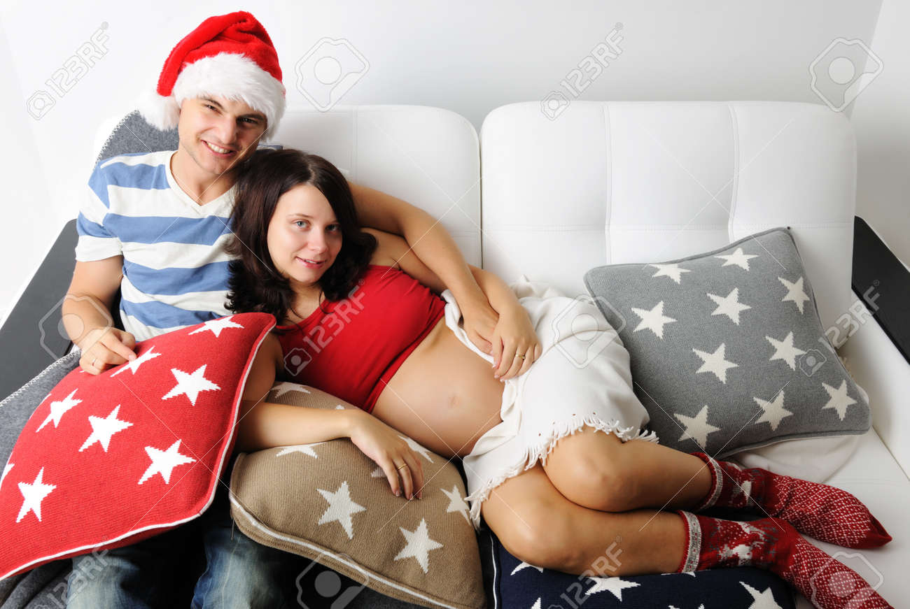 Happy pregnant couple at christmas on a sofa Stock Photo - 10438670