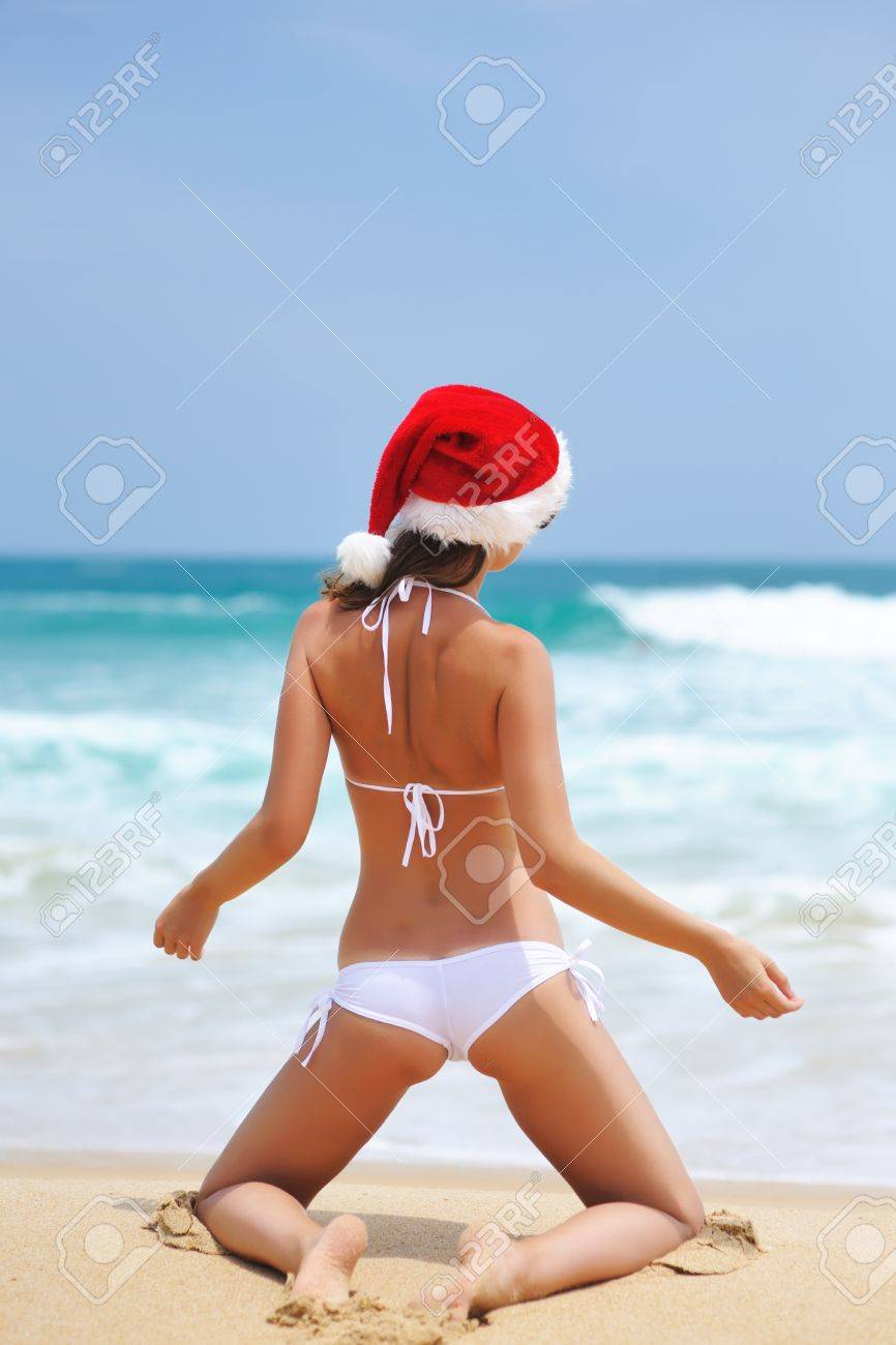 Woman on the beach in santa's hat Stock Photo - 10784895