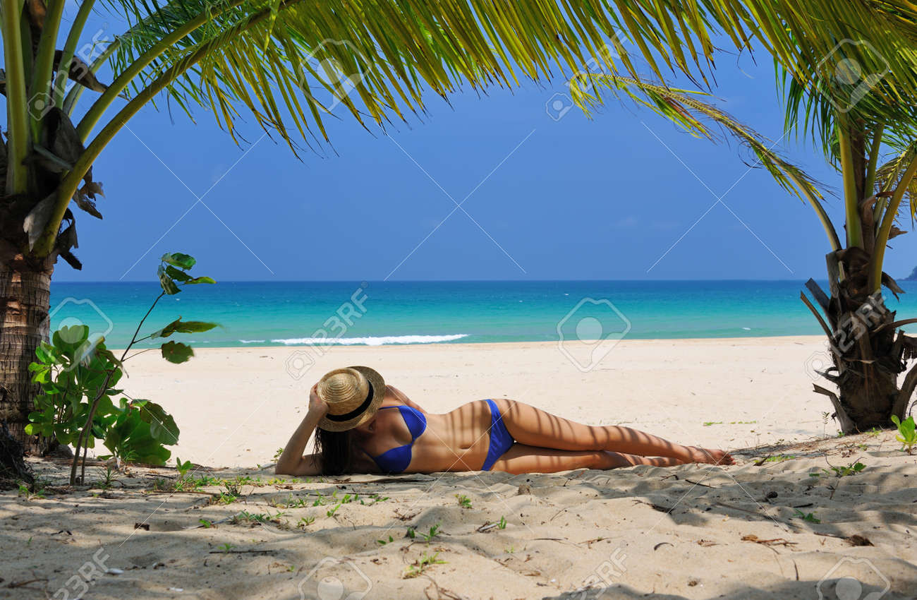Woman at beach under palm tree with leaf shadow on her body woman at beach under palm tree with leaf shadow on her body 18738360 voltagebd