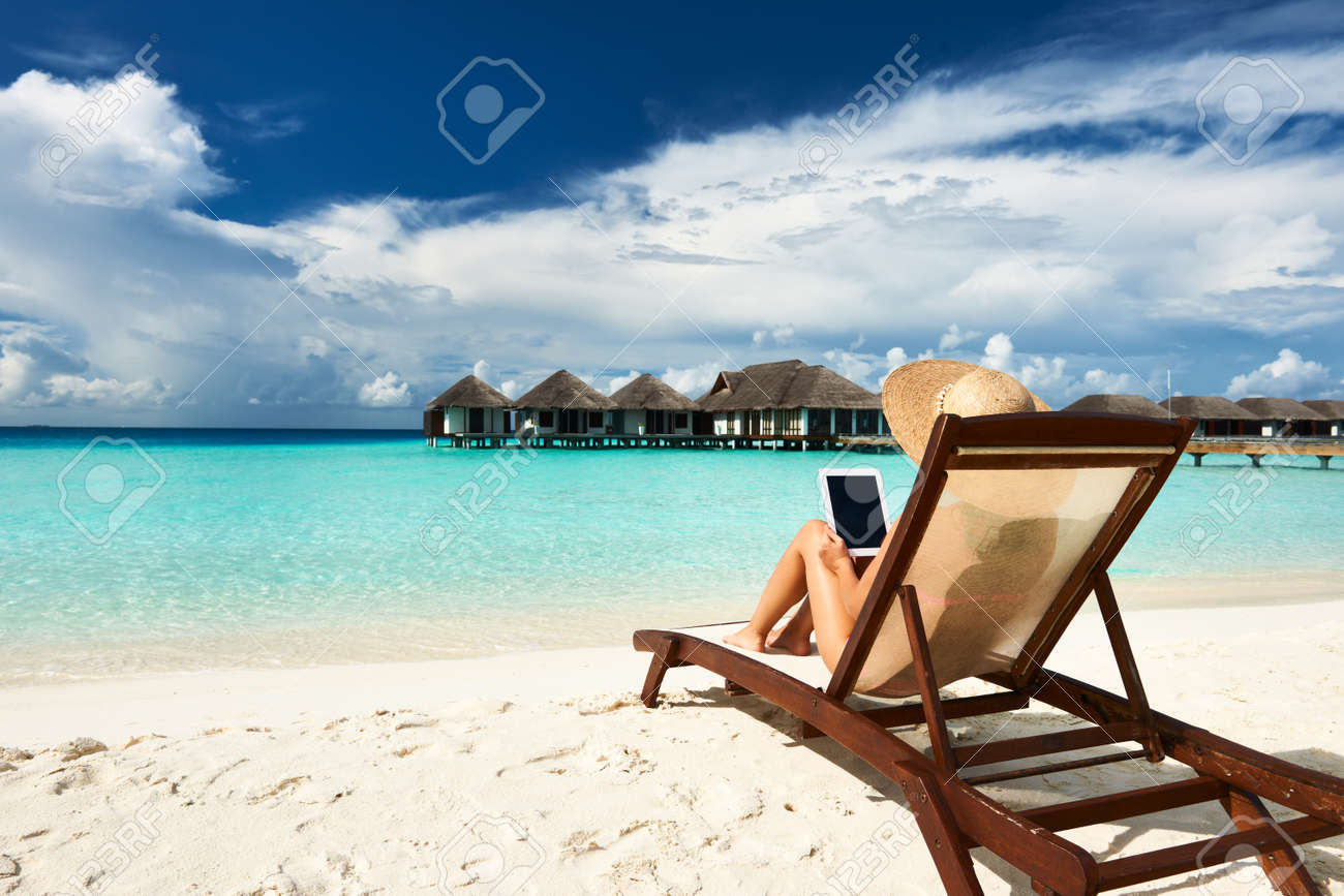 Young woman in hat with tablet pc at the beach Stock Photo - 19837730