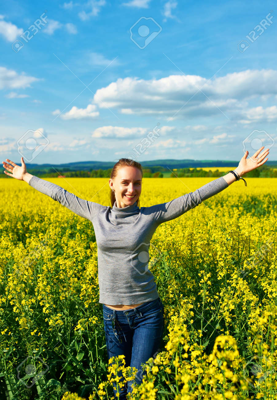 Girl with outstretched arms at colza field Stock Photo - 23092935