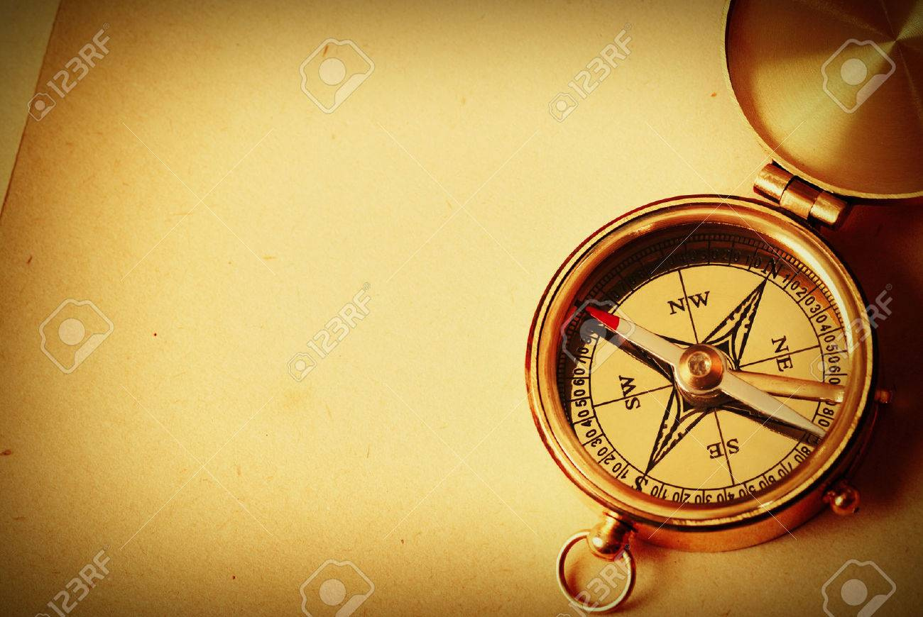 antique brass compass over old map background stock photo 44813393