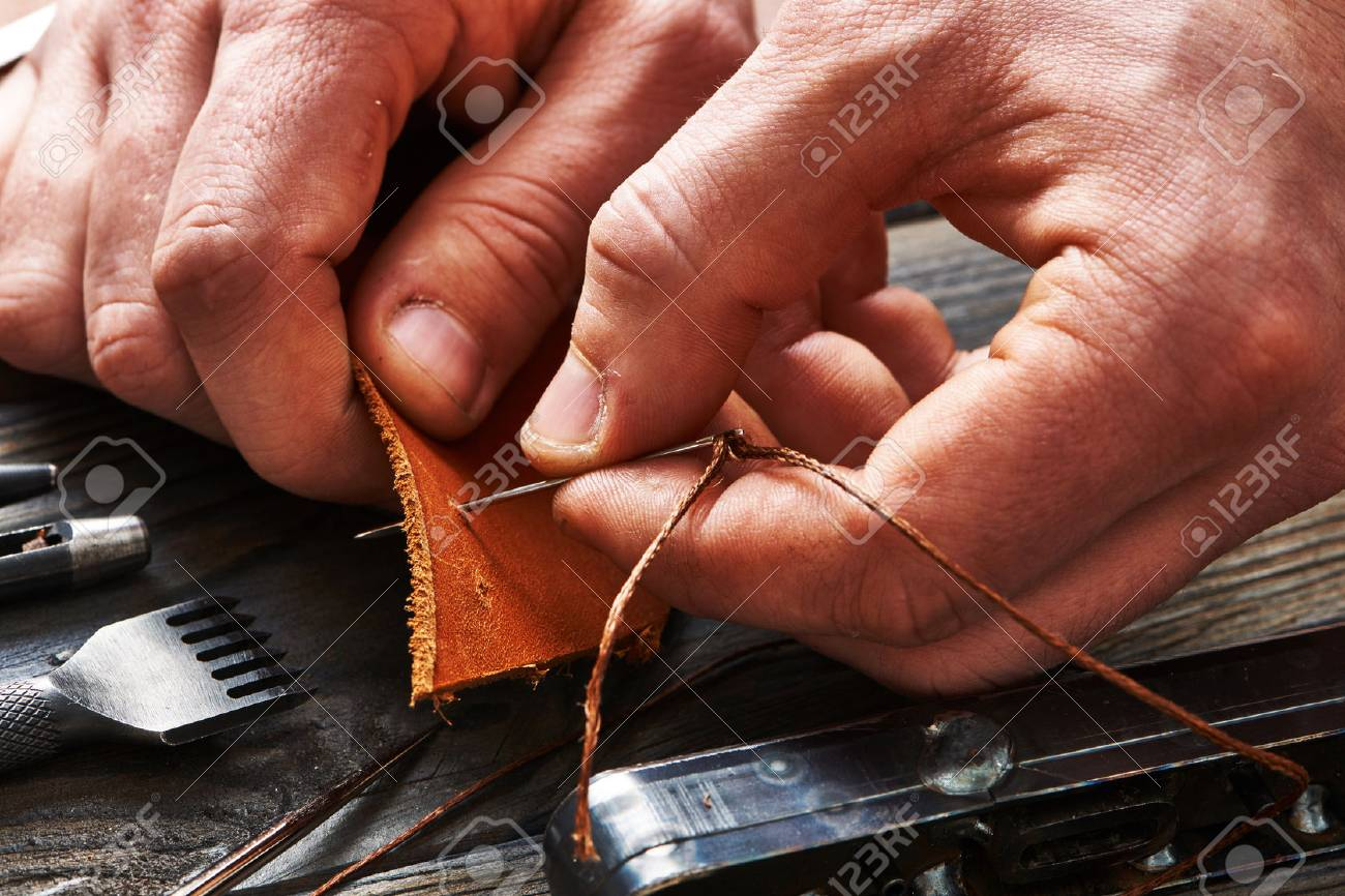 Man working with leather using crafting DIY tools - 52209001