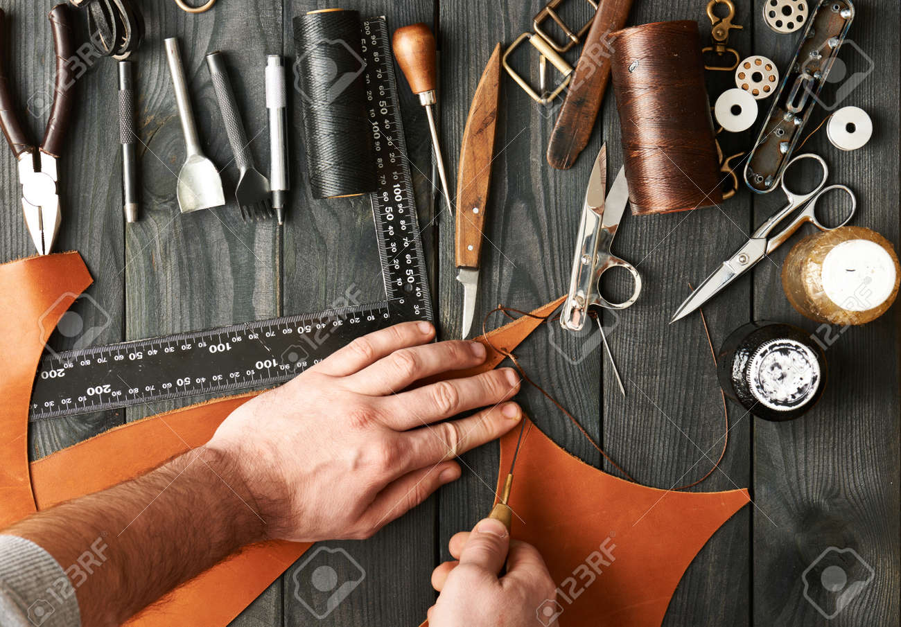 Man working with leather using crafting DIY tools - 52780524