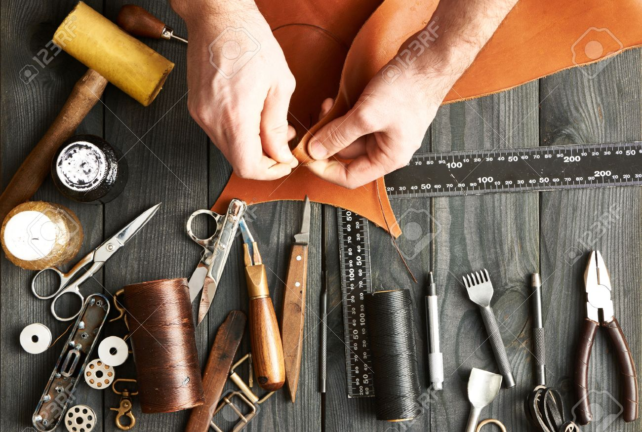 Man working with leather using crafting DIY tools - 52916325