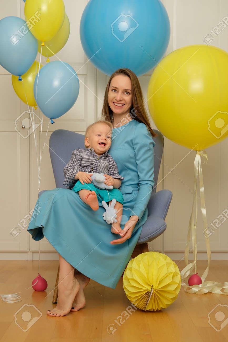 Verjaardag Peuter.Een Jaar Oude Babyjongen Eerste Verjaardag Peuter Kind Met Moeder Zit In Stoel En Plezier Met Ballonnen