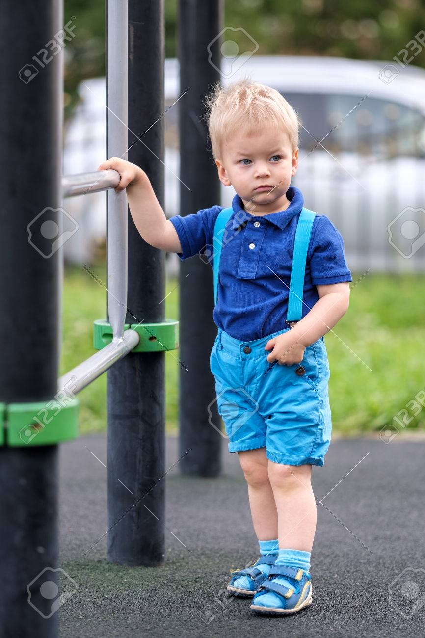 277373bf5612 Portrait of toddler child outdoors wearing shorts and suspenders. One year  old baby boy at