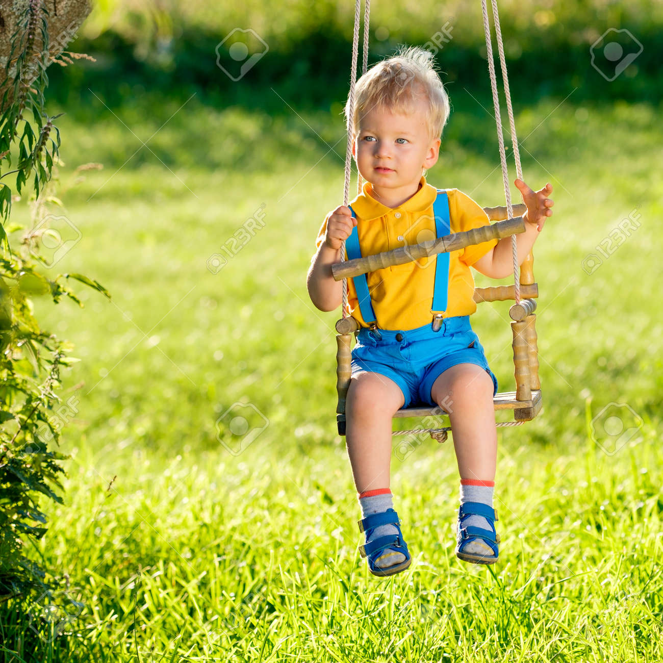 Portrait of toddler child swinging outdoors. Rural scene with one year old  baby boy at