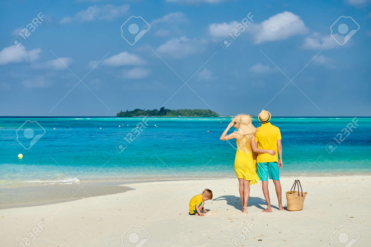 Family on beach, young couple in yellow with three year old boy. Summer vacation at Maldives. - 122398620