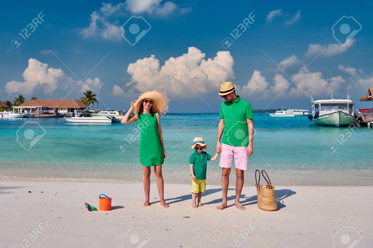 Family on beach, young couple in green with three year old boy. Summer vacation at Maldives. - 124965429