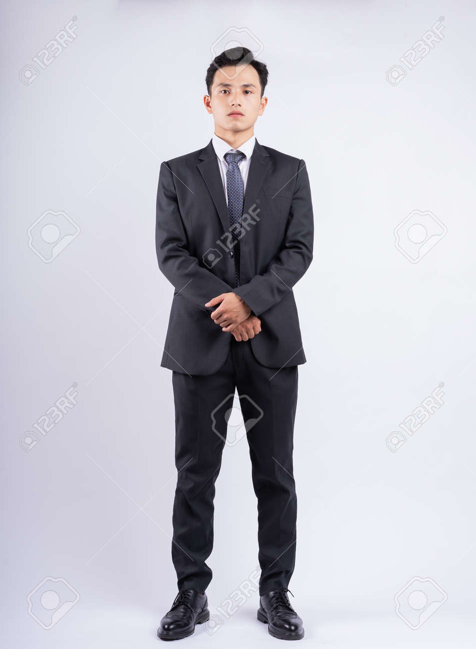 Young Asian businessman standing on white background - 167977955