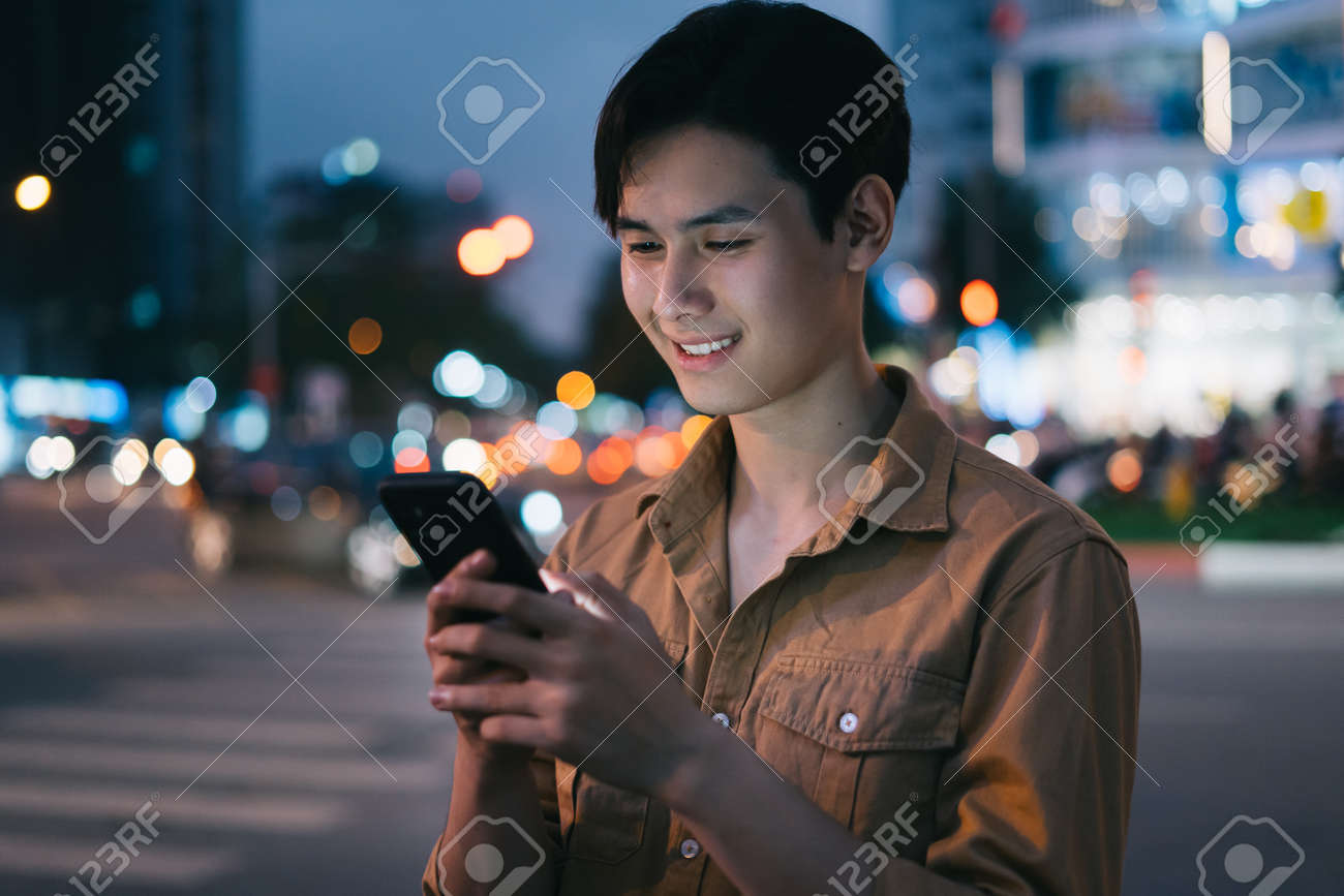 Young Asian man is using his phone while walking in the street at night - 167978139