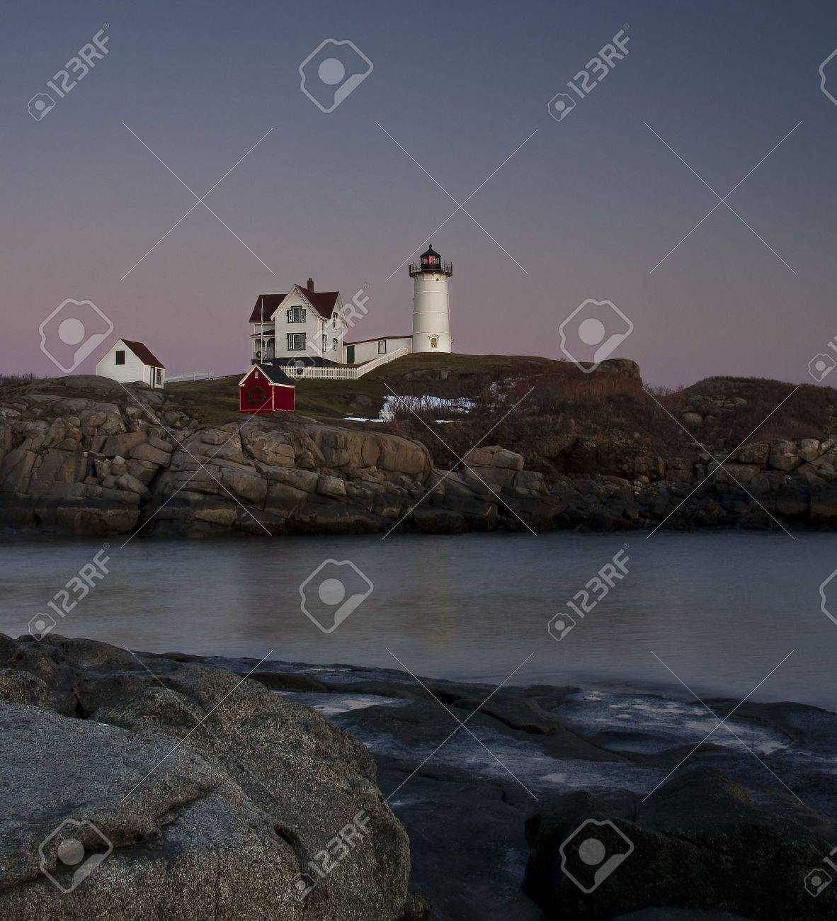 lighthouse at cape neddick main near sunset with christmas decorations stock photo 4973621