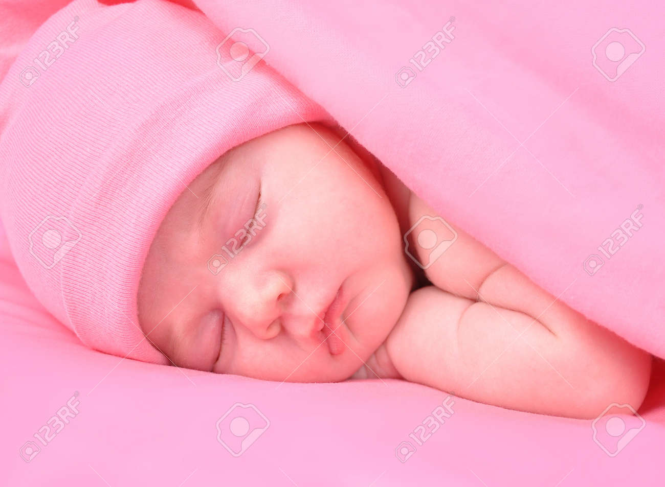 A newborn baby girl is sleeping on a pink background with a blanket  She is wearing a hat  Use it for a childhood, parenting  or innocence theme Stock Photo - 15075799