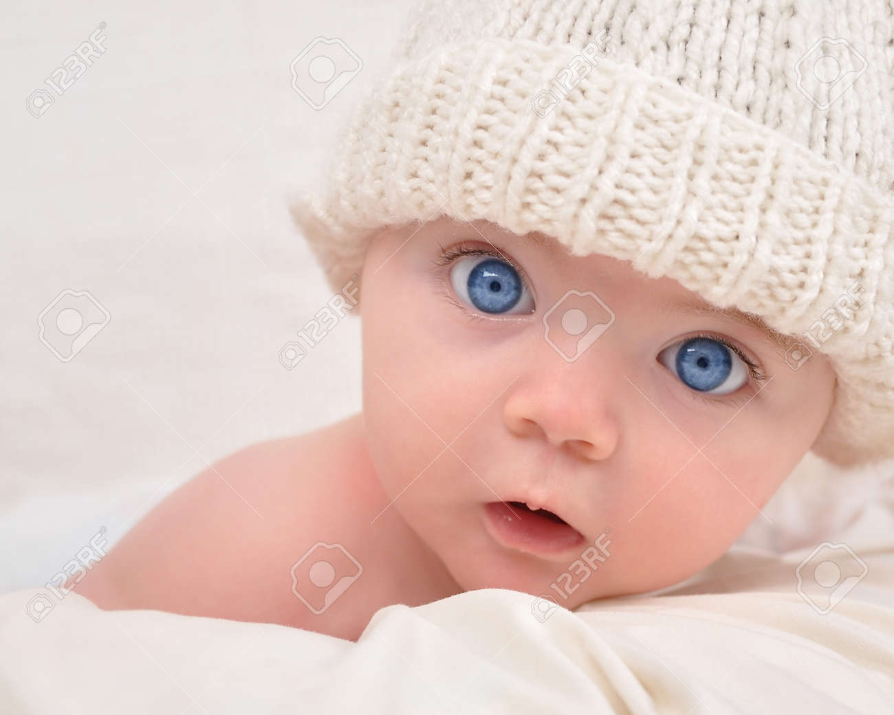 A cute little baby is looking into the camera and is wearing a white hat  The baby could be a boy or girl and has blue eyes  use it for a parenting or love concept Stock Photo - 15125216