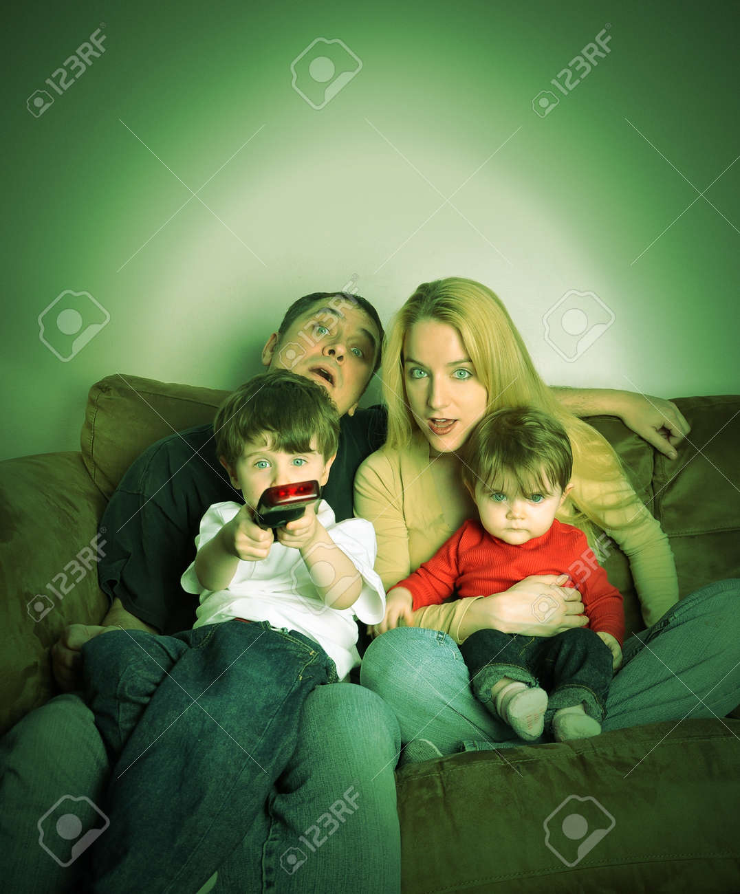 A family is watching television together on a couch and look shocked at what they see. Stock Photo - 17343940