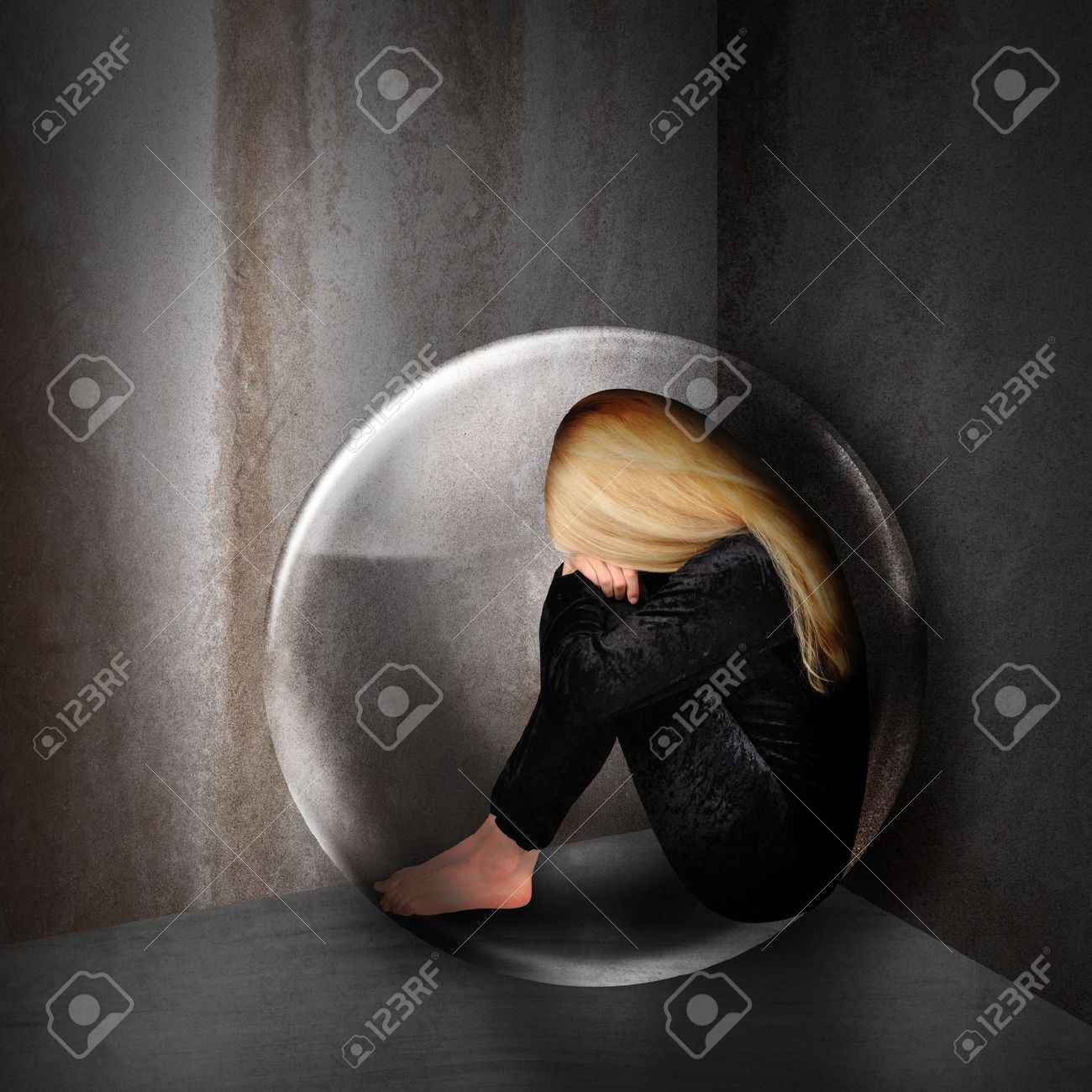 A young woman is depressed and sad in a bubble in a dark room  The girl has her head down and curled up in a corner Stock Photo - 17352554