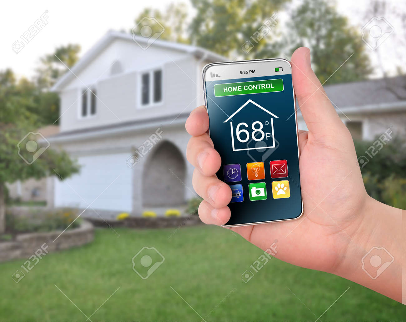 A smart phone is in front of a house with various home control icons like temperature and time Stock Photo - 18522444