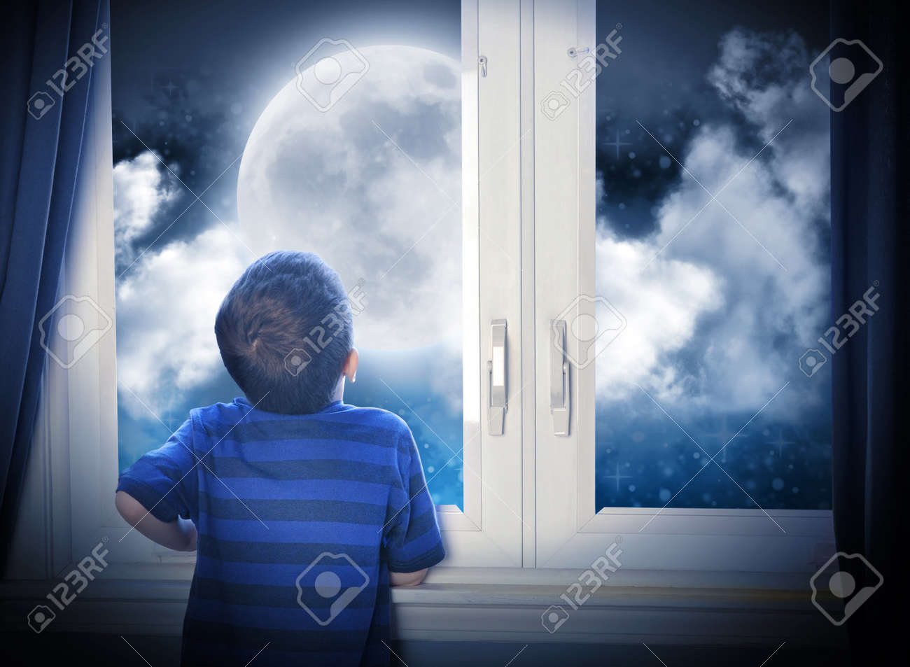 A young boy is looking out of the window at a big moon in the dark night with stars and space for an astronomy or imagaination concept Stock Photo - 20674943