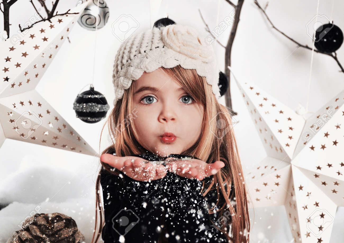 Foto de archivo - Un niño pequeño está soplando los copos de nieve en una  escena de fondo del estudio con estrellas y adornos de Navidad para un  concepto ... ae7d70ee5a9