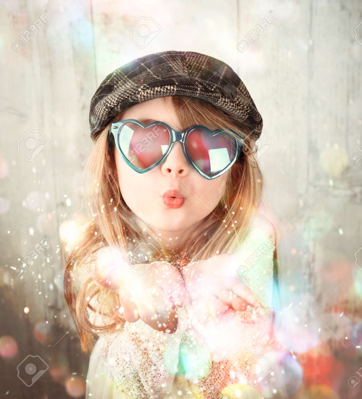 84e29b86731 A little child is wearing sunglasses and blowing magical rainbow glitter  sparkles in the air for