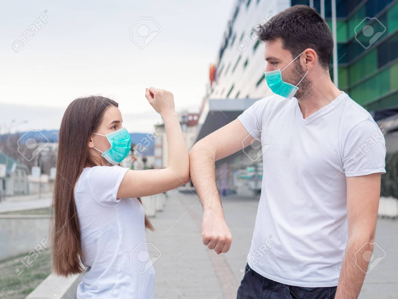 Two people woman and man wearing medical mask, friends greet each other with their elbows, instead of shaking hands. Elbow bump. A new greeting way to avoid the spread of coronavirus. - 143409686