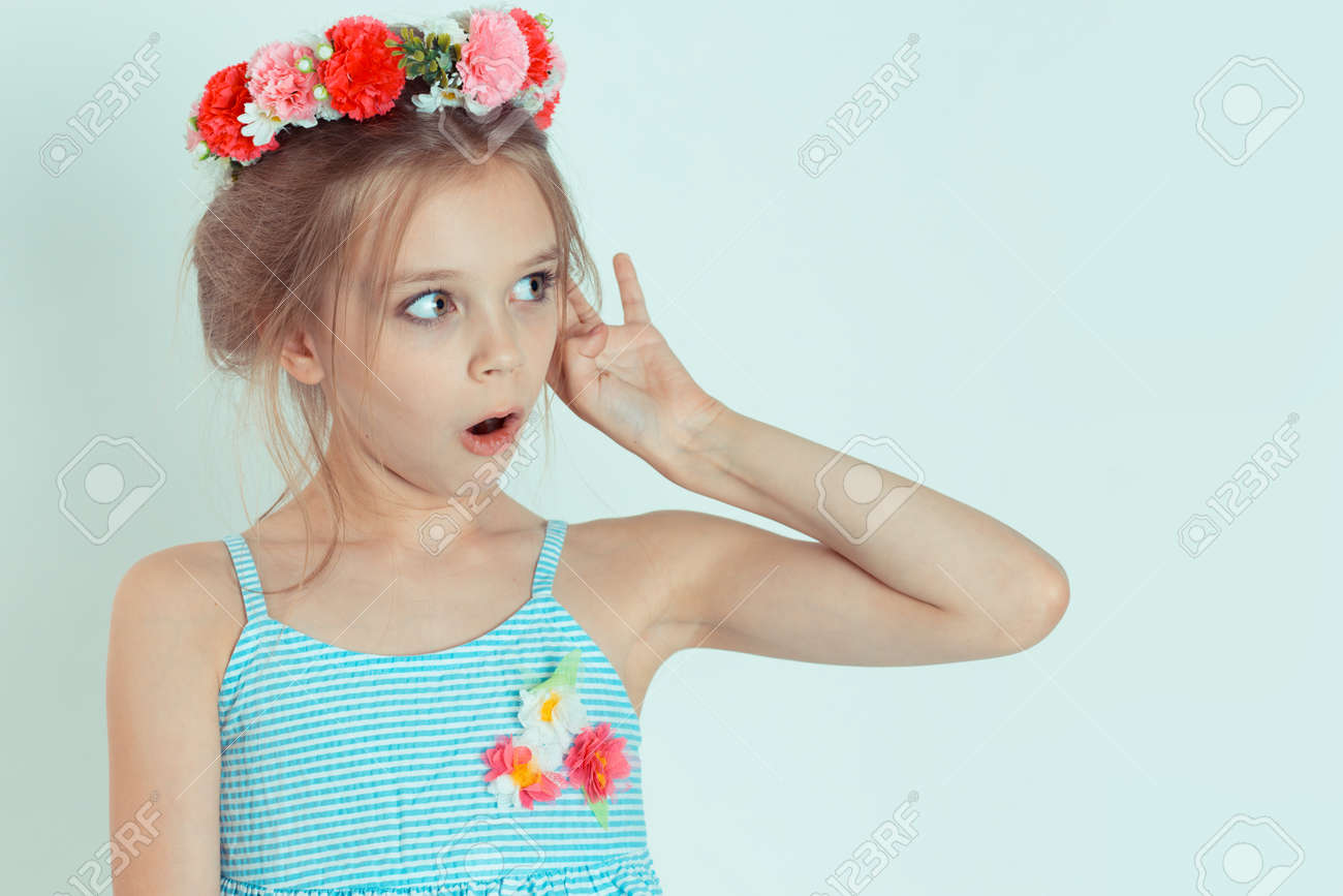 Shocked kid girl hand to ear eavesdropping listening to shocking news. Closeup portrait of Caucasian kid model with floral headband isolated on white blue gray copy space background. Horizontal image - 144106942