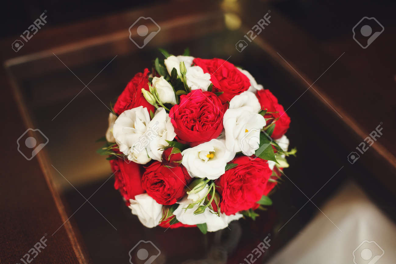 Beautiful Wedding Bouquet Of Red And White Roses On Table Stock